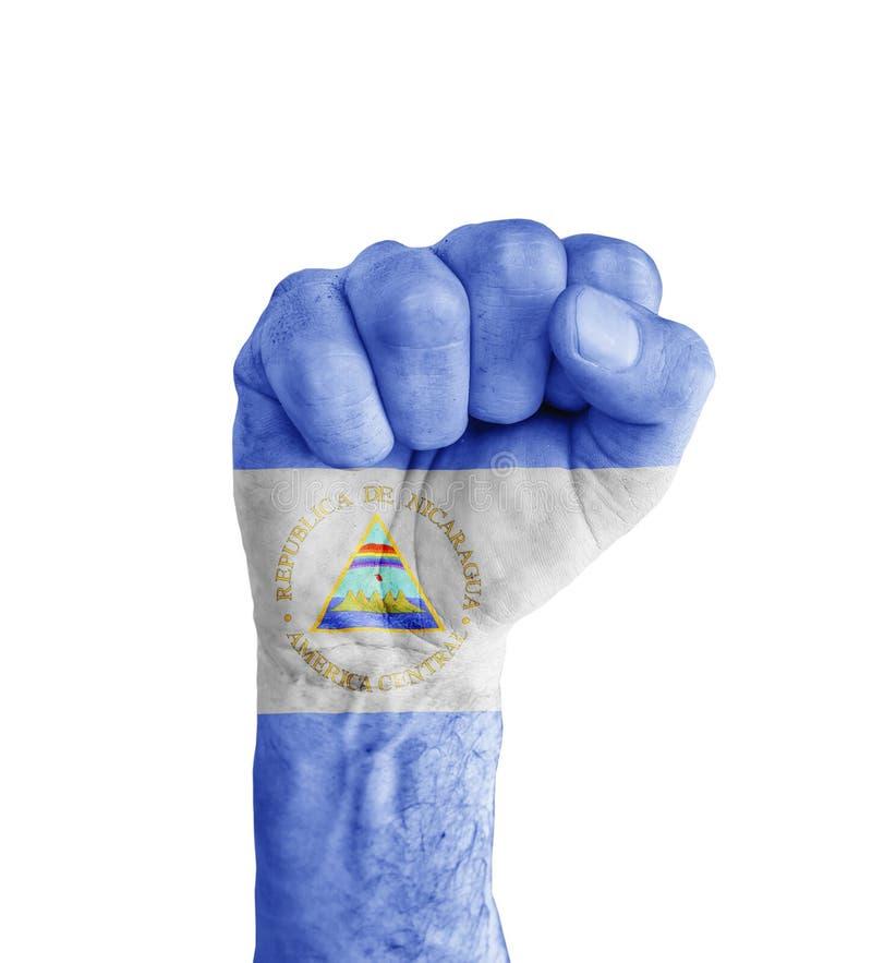 Vlag van Nicaragua op menselijke vuist zoals overwinningssymbool dat wordt geschilderd stock fotografie