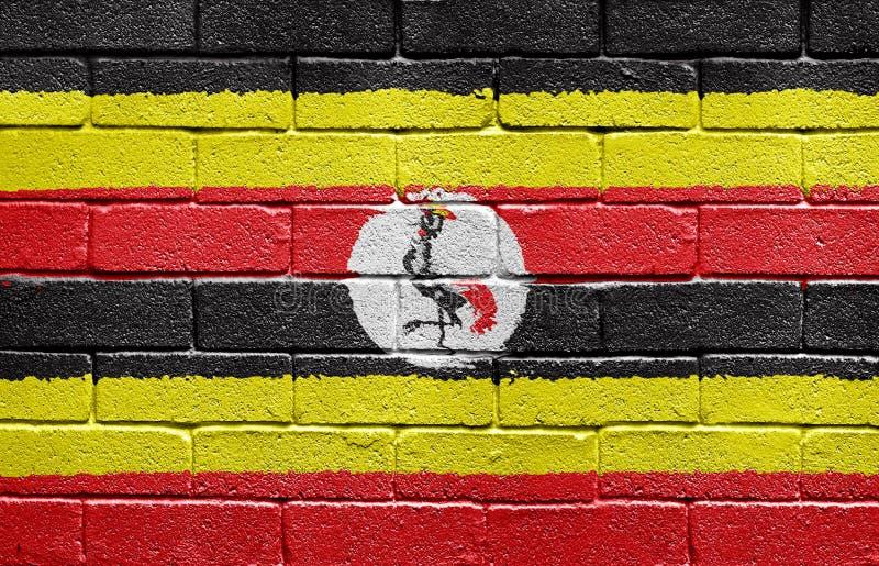Vlag van Oeganda op bakstenen muur stock afbeeldingen