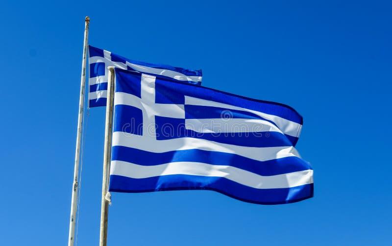 Vlaggen die van Griekenland in Wind en Blauwe Hemel vliegen royalty-vrije stock afbeeldingen