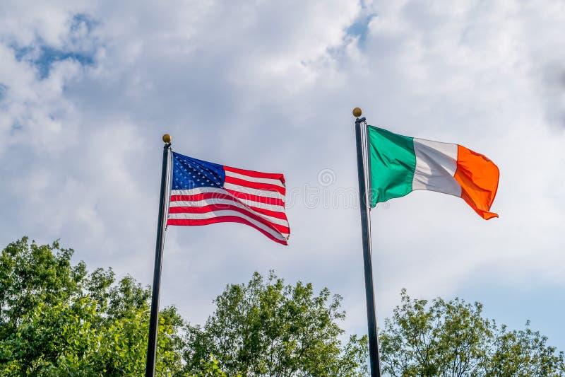 Vlaggen die van Verenigde Staten en Irland tegen blauwe hemel, dichtbij Iers de hongersnoodgedenkteken van Rhode Island fladderen stock foto's