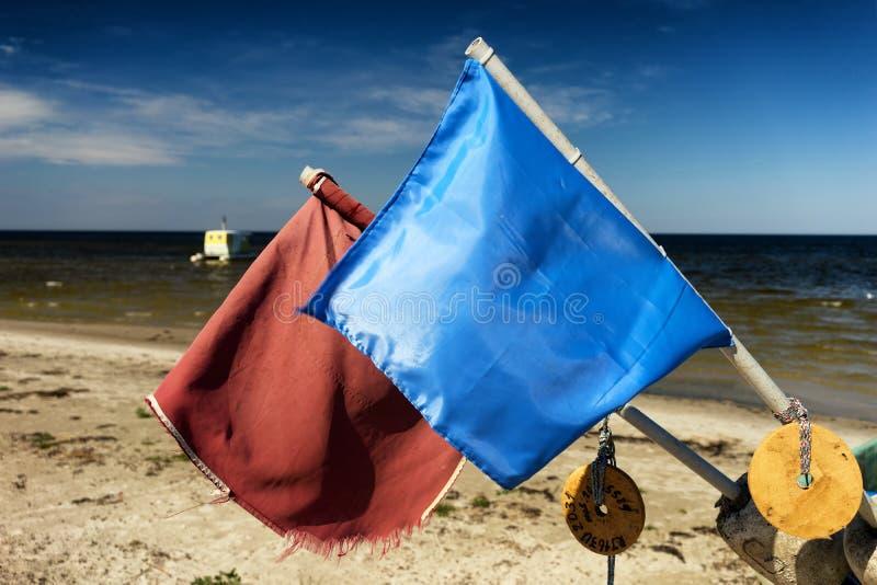 Vlaggen op de vissersboten op de kust van de Oostzee stock foto