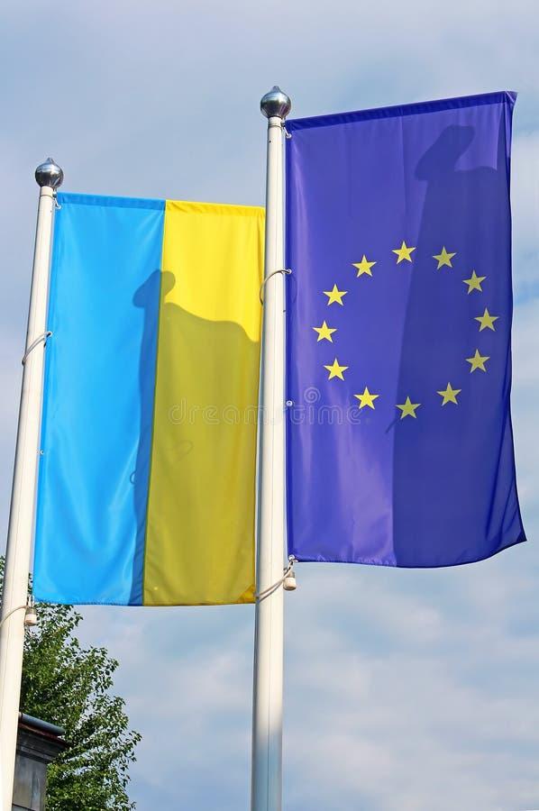 Vlaggen van de EU en de Oekraïne op de vlaggestok stock foto