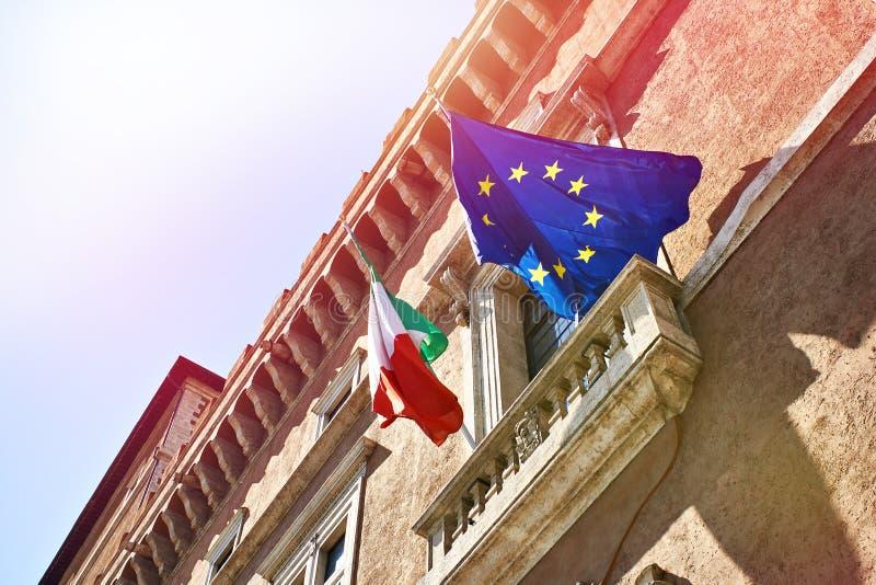 Vlaggen van de Europese Unie van Italië en tegen blauwe hemel als achtergrond stock fotografie