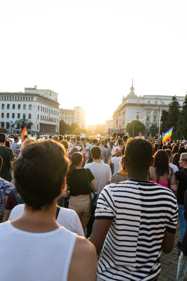 Vlaggen van de menigte de Golvende Regenboog in Pride Parade Mensen die een Vrolijke trots bijwonen Maart met homosexuelen en les royalty-vrije stock afbeelding