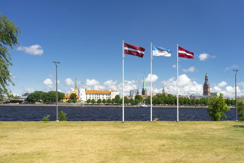 Vlaggen van Letland en de stad van Riga op de waterkant stock foto's