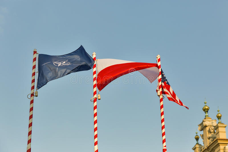 Vlaggen van NAVO, Polen en de V.S. openlucht tegen duidelijke blauwe hemel royalty-vrije stock afbeeldingen