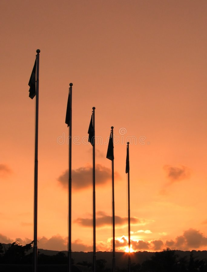 Vlaggestokken en Zonsondergang stock foto's