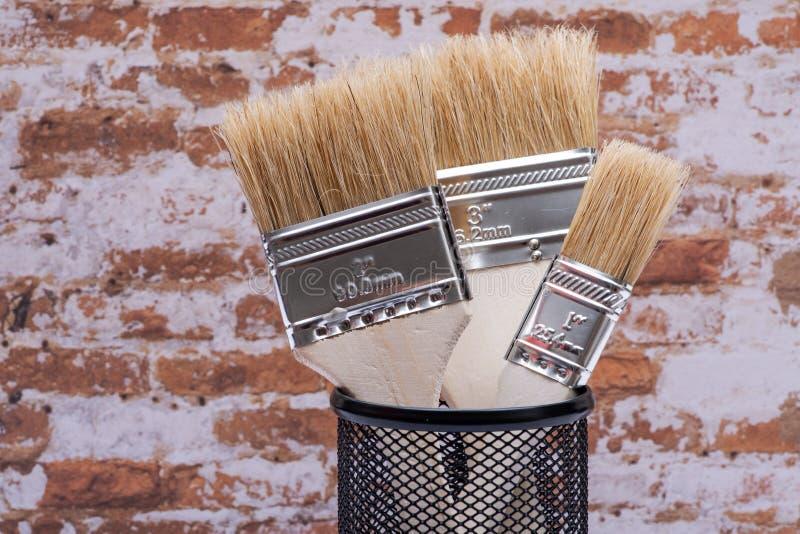 Vlak die Chip Painting Brush op bakstenen muur wordt ge?soleerd royalty-vrije stock foto's