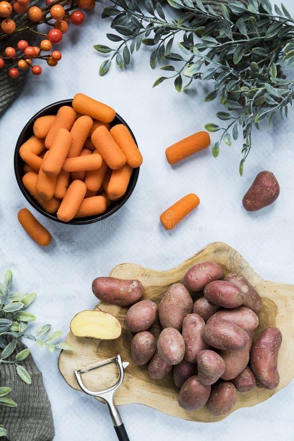 Vlak leg aardappels op scherpe raad en wortelen in kom stock foto