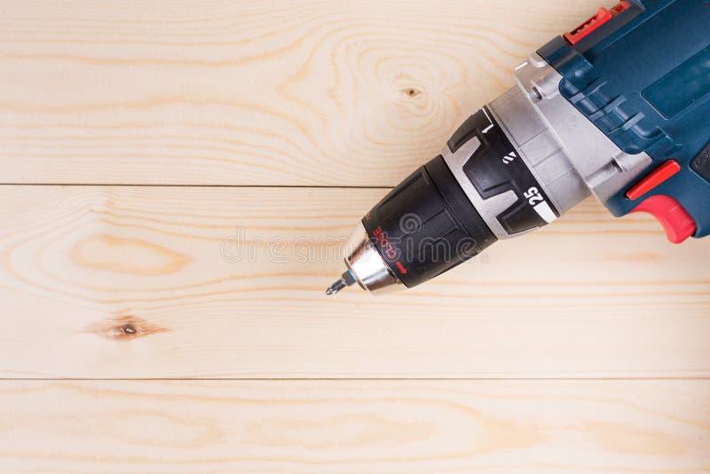 Vlak leg accu draadloze boor met batterij ten laste op de houten raad met exemplaarruimte stock fotografie