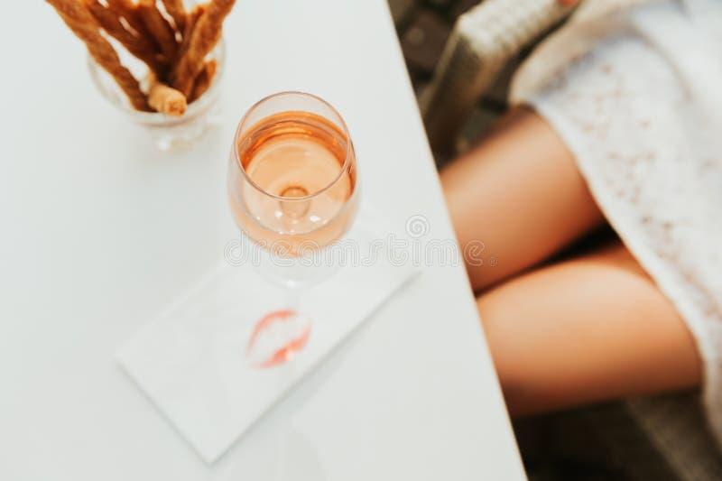 Vlak leg beeld van roze wijn en vrouwenbenen stock foto's