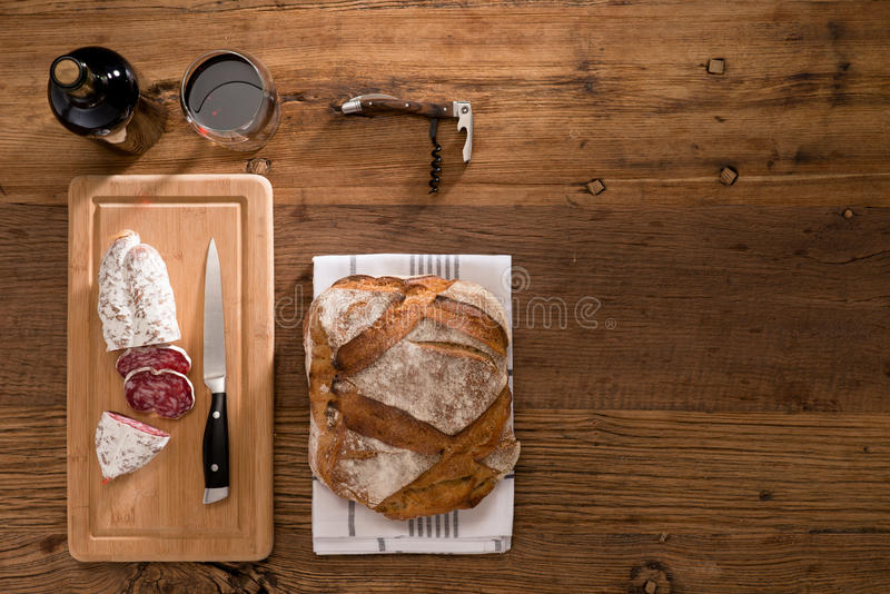 Vlak leg boven mening van droge worstdelicatessen gesneden vlees met wijn en traditioneel brood op houten raad stock foto's