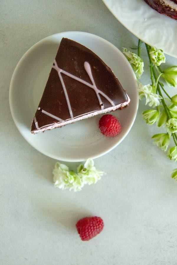 Vlak leg chocolade en frambozenstuk van cake op een witte plaat met witte bloemen en verse bessen royalty-vrije stock foto's