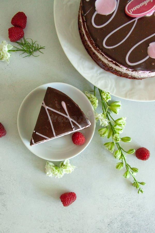 Vlak leg chocolade en frambozenstuk van cake op een witte plaat met witte bloemen en verse bessen royalty-vrije stock foto