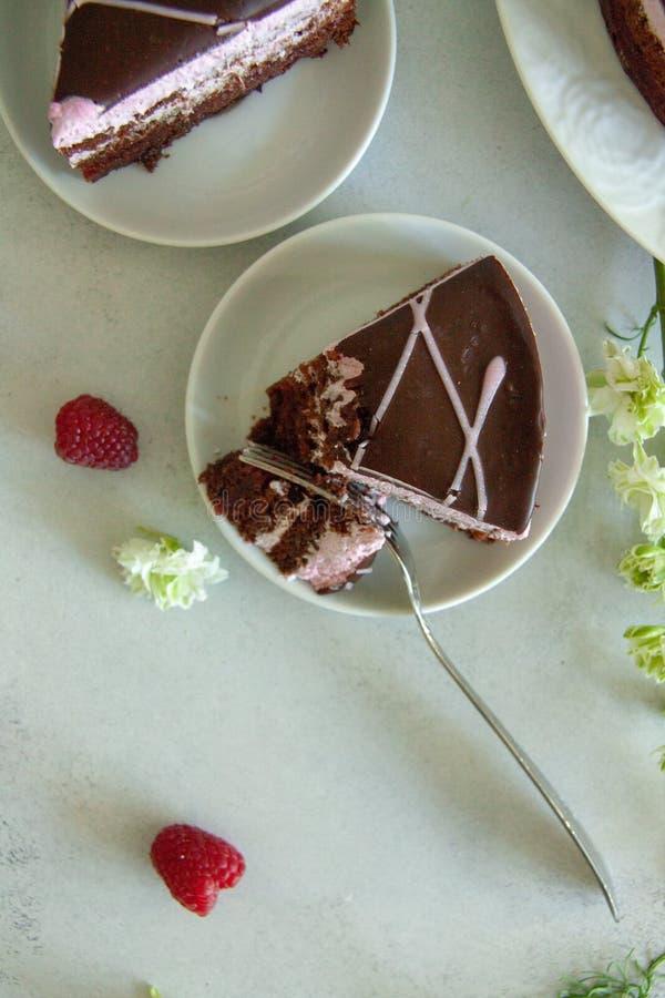 Vlak leg chocolade en frambozenstuk van cake op een witte plaat met witte bloemen en verse bessen stock afbeelding