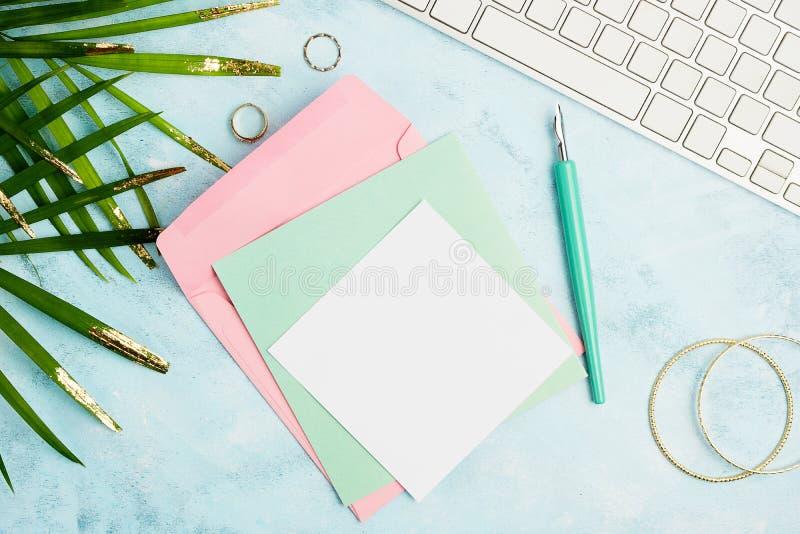 Vlak leg de achtergrond van de groetkaart: wit toetsenbord, envelop, ambachtdocument met vulpen en tropische bladeren op blauwe a royalty-vrije stock foto