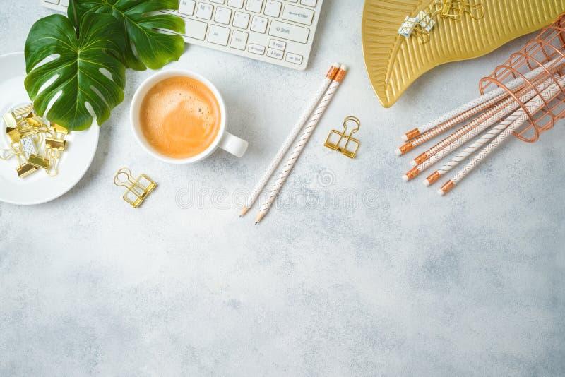 Vlak leg de vrouwelijke lijst van het huisbureau met koffiekop, gouden toebehoren, computertoetsenbord en tropische bladeren op g royalty-vrije stock afbeeldingen
