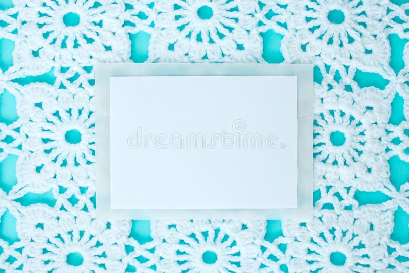 Vlak, leg, een blad van document voor tekst op een blauwe achtergrond met gehaakt wit uitstekend kant, de winterthema, vierkant o stock foto