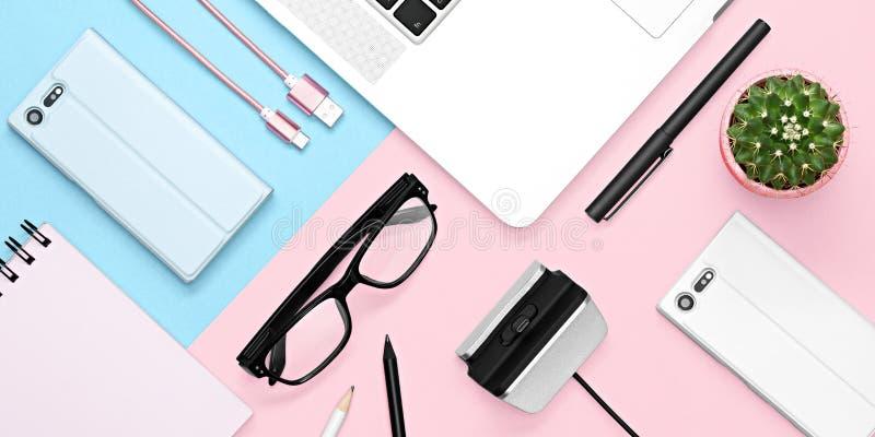 Vlak leg foto van bureau met geval voor telefoon en tablet, notitieboekje, theemok, potlood en pen, cactus, roze en blauwe achter stock foto