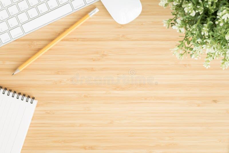 Vlak leg foto van bureau met muis en toetsenbord, Hoogste mening workpace over bamboe houten lijst en exemplaarruimte stock foto's