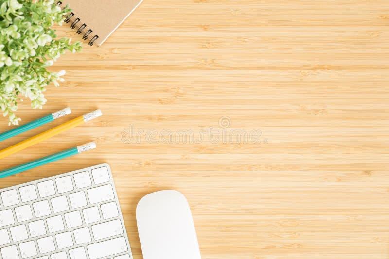 Vlak leg foto van bureau met muis en toetsenbord, Hoogste mening workpace over bamboe houten lijst en exemplaarruimte stock afbeeldingen