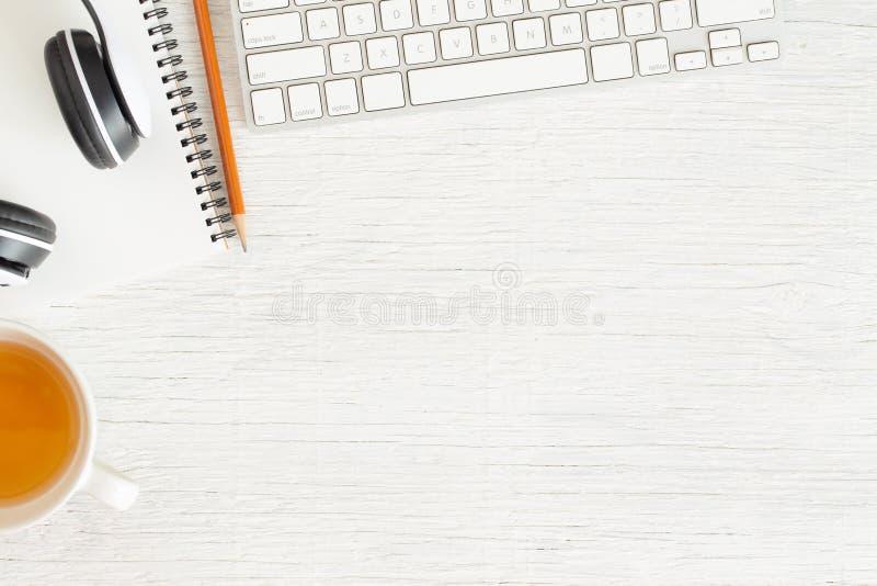Vlak leg foto van bureau met Oortelefoon en toetsenbord, Exemplaarruimte op witte achtergrond met notitieboekje en potlood, thee stock foto