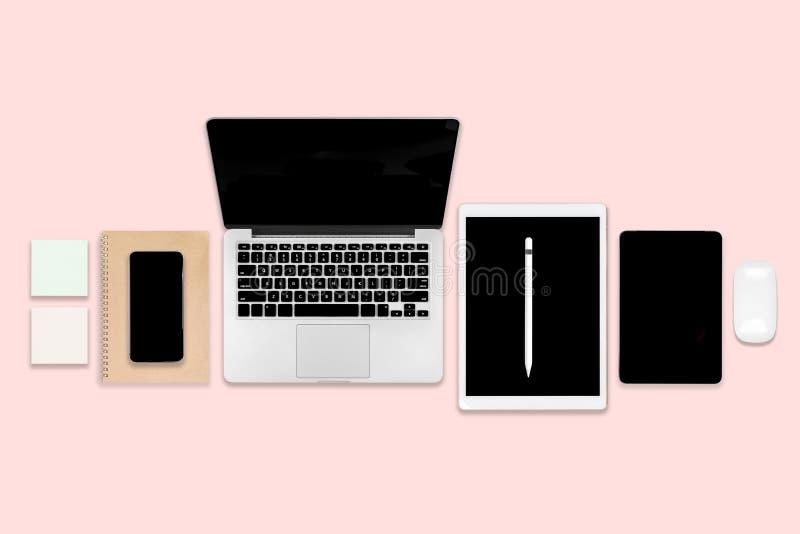 Vlak leg foto van bureaulijst met laptop computer, digitale tablet, mobiele telefoon en toebehoren op moderne roze toonachtergron royalty-vrije stock foto's