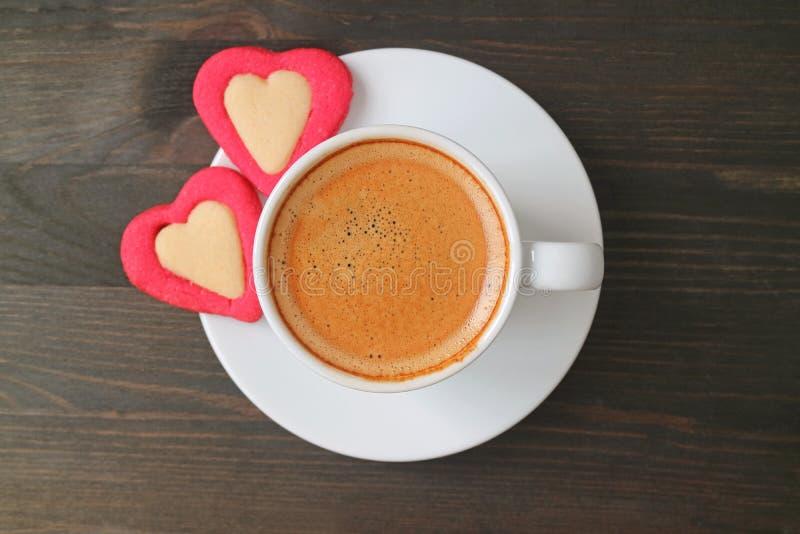 Vlak leg foto van een espresso met twee hart gevormde die koekjes op donkere bruine houten lijst worden gediend royalty-vrije stock foto's