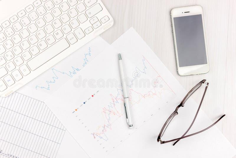 Vlak leg foto van wit bureau met laptop, smartphone, oogglazen, notitieboekje en pen met exemplaar ruimteachtergrond Model stock fotografie