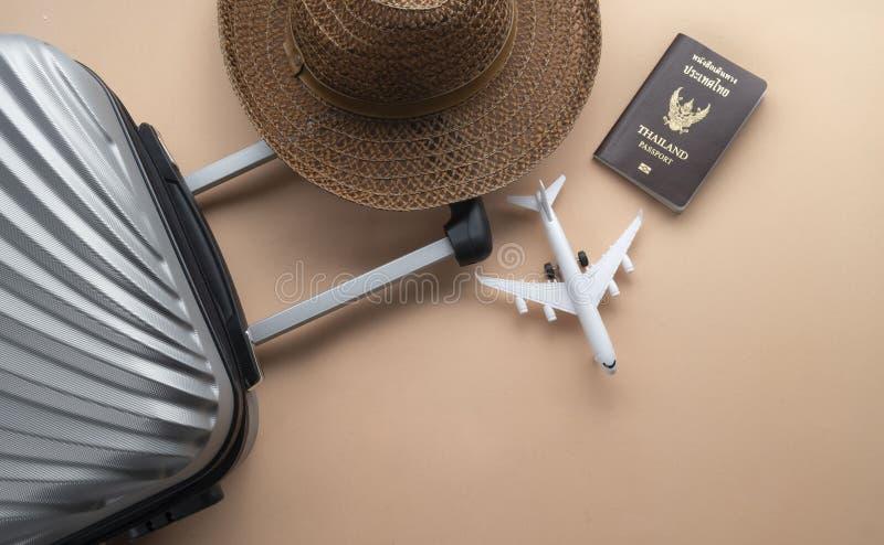 Vlak leg grijze koffer met bruine hoed, het minivliegtuig en Paspoort van Thailand op pastelkleurachtergrond reisconcept - Beeld stock afbeeldingen