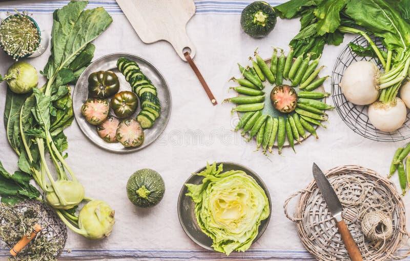 Vlak leg groene groenten in kommen op lichte lijst met mes: groene erwten, koolraap, sla, courgette, komkommer, groene tomaten stock afbeelding