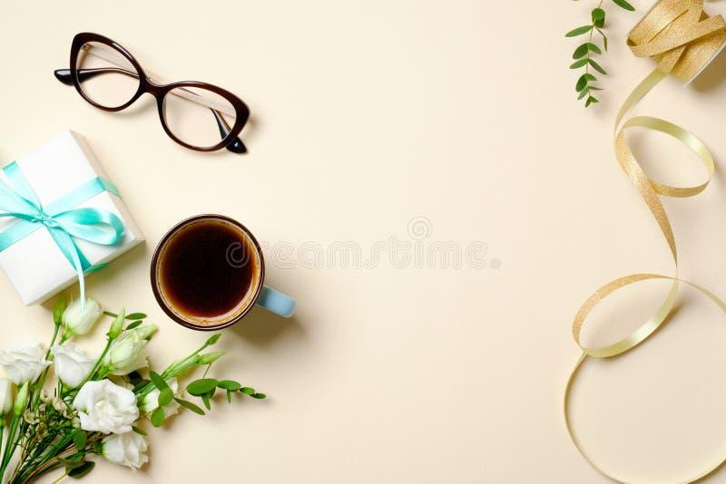 Vlak leg het bureau van het vrouwenhuis met giftdoos, koffiekop, glazen, het boeket van rozenbloemen, lint en vrouwelijke gouden  royalty-vrije stock afbeelding