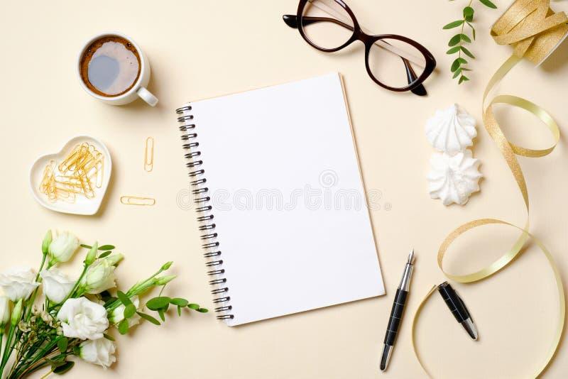 Vlak leg het bureau van het vrouwenhuis met koffiekop, blocnote, paperclip, het boeket van rozenbloemen, lint en vrouwelijke goud royalty-vrije stock fotografie