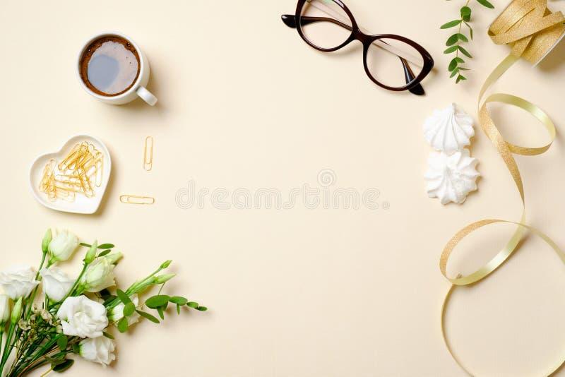 Vlak leg het bureau van het vrouwenhuis met koffiekop, glazen, het boeket van rozenbloemen, paperclip, lint en vrouwelijke gouden stock afbeeldingen
