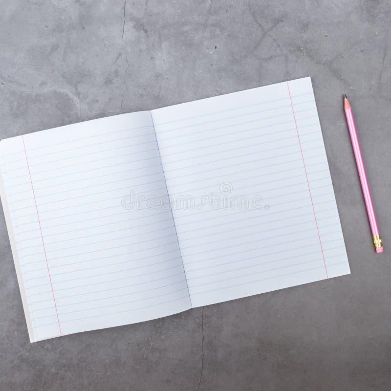 Vlak leg, hoogste mening, notitieboekje, potlood over een grijze geweven achtergrond stock fotografie