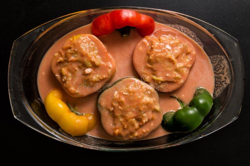 Vlak leg, hoogste mening Sluit omhoog Het koken van een Bulgaars Traditioneel Diner Gevulde groene paprika's in tomaat sause stock afbeeldingen