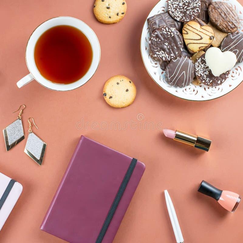 Vlak leg huisbureau Vrouwelijke werkruimte met agenda, bloemen, snoepjes, maniertoebehoren Manier blogger concept royalty-vrije stock foto