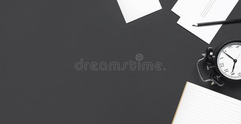 Vlak leg kop zwarte van het het notitieboekjepotlood van de koffie zwarte wekker open witte kaarten op grijs donker achtergrond h stock fotografie