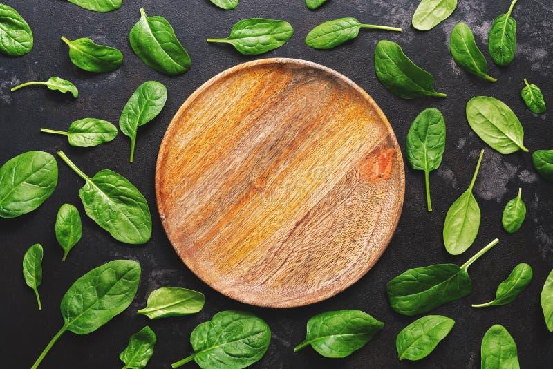 Vlak leg lege houten plaat en verse spinaziebladeren op een donkere achtergrond Hoogste mening royalty-vrije stock afbeelding
