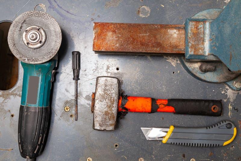 Vlak leg mening van een werkbank met een reeks hulpmiddelen die uit een grote zware bankschroef, hoekmolen, schroevedraaier, snij stock foto's