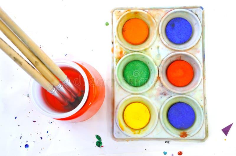 Vlak leg mening van waterkleuren en verfborstel op een witte backgr stock afbeelding