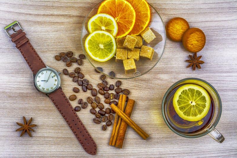Vlak leg Mensen` s horloges met leerriem Plakken van citroen en sinaasappel op een schotel Kop thee met citroen Koffiebonen, koek stock foto's
