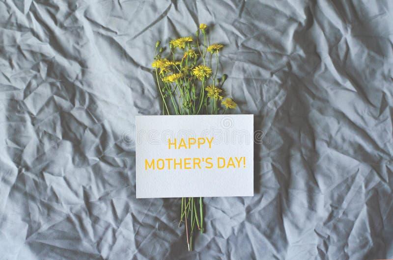 Vlak leg met bloemen en een prentbriefkaar van gelukwensen op de dag van een gelukkige moeder stock fotografie