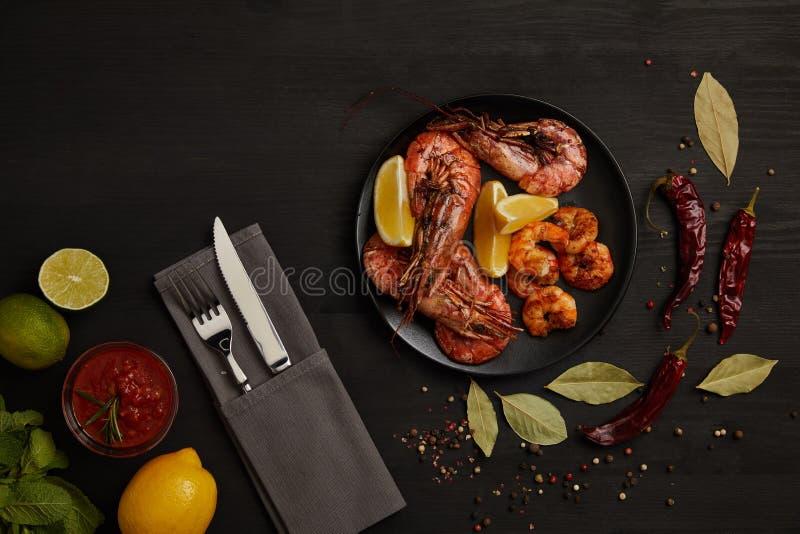 vlak leg met geroosterde garnalen met citroenstukken op plaat en geschikte saus, kruiden, ingrediënten en bestek rond op zwarte s royalty-vrije stock foto