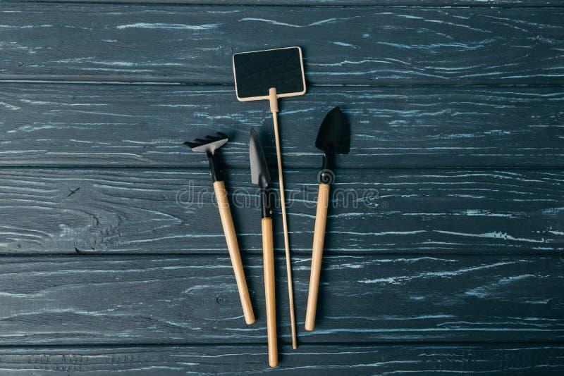 vlak leg met geschikte het tuinieren hulpmiddelen en leeg bord stock afbeelding
