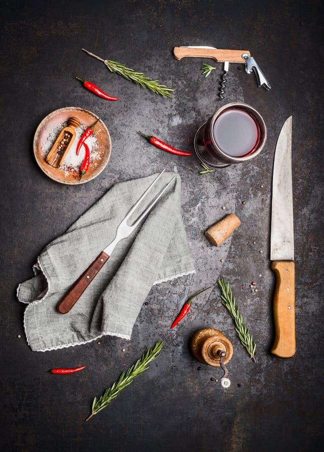 Vlak leg met keuken kokende hulpmiddelen, glas rode wijn, kruiden en kruiden op donkere rustieke achtergrond royalty-vrije stock foto