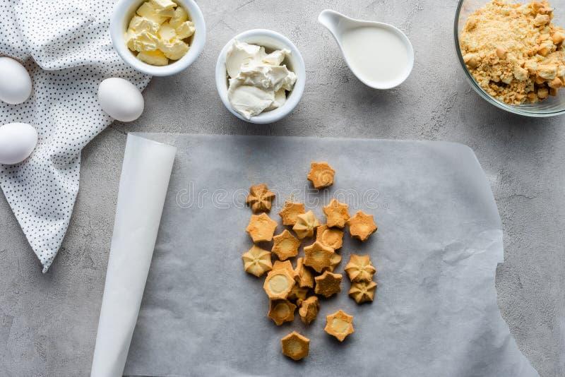 vlak leg met koekjes, ruwe kippeneieren, boter en zure room voor het maken van pastei geschikt stock afbeelding