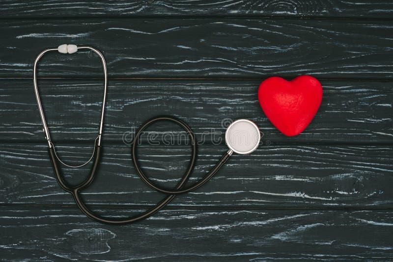 vlak leg met rode hart en stethoscoop op donker houten tafelblad, de dagconcept van de wereldgezondheid stock afbeeldingen