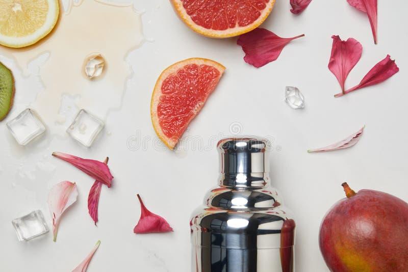 vlak leg met shaker, ijsblokjes, bloembloemblaadjes en geschikte exotische vruchten op wit tafelblad royalty-vrije stock afbeelding