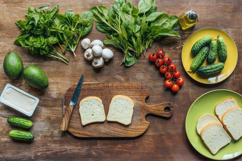 vlak leg met stukken brood, roomkaas en geschikte verse groenten stock foto's